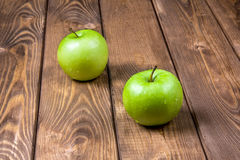 Two green apples on a wooden background. Two green apples on a brown wooden background Royalty Free Stock Photos