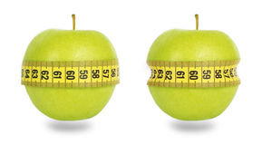 Two green apples and yellow measuring tape Stock Images