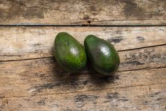 Two Green Avocado on Wood Board Royalty Free Stock Images