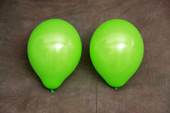 Two green balloons against brown wallpaper Stock Image
