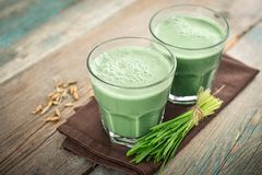 Two green barley grass shots. With blades of young barley on a wooden background Stock Photo