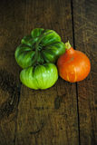 Two Green beef tomatoes and a red kuri sash on a dark wooden table Royalty Free Stock Photography