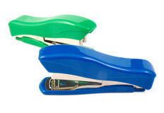 Two green and blue staplers on a white background Royalty Free Stock Photo
