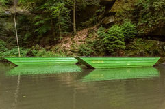 Two green boats floating over a water body Stock Images