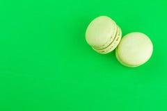 Two green cake macaron on green background, maccarone sweet dessert Stock Photos