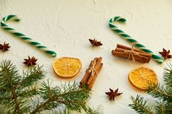 Two green candy cones and traditional holiday spices: anise stars, sticks of cinnamon, dried oranges on white concrete background Royalty Free Stock Photos