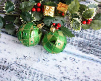 Two green Christmas Balls and Holly leaves Royalty Free Stock Photography