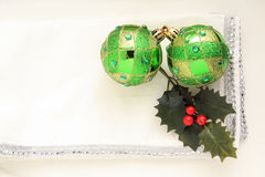 two green Christmas balls on a white and silver napkin Royalty Free Stock Photography