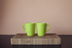 Two green cups on wooden cutting board. Frontal view of two big cups of coffee on wooden cutting board Royalty Free Stock Images