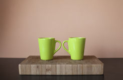 Two green cups on wooden cutting board. Frontal view of two big cups of coffee on wooden cutting board with handles touching Royalty Free Stock Photos