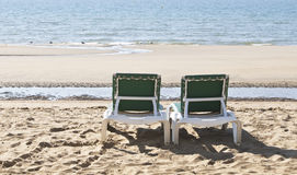 Two green deckchairs overlooking the sea. Two deckchair recliners on the beach overlooking the sea Royalty Free Stock Photography