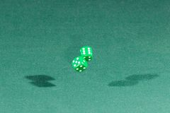 Two green dices falling on a green table. Two green dices falling on a isolated green table stock photo