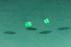 Two green dices falling on a green table. Two green dices falling on a isolated green table stock photography