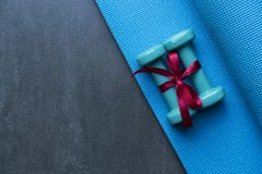 Two green dumbbell with red gift bow on blue yoga mat Royalty Free Stock Photo