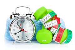 Two green dumbells, tape measure and alarm clock. Fitness and he stock images