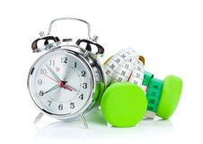 Two green dumbells, tape measure and alarm clock. Fitness and he Royalty Free Stock Images