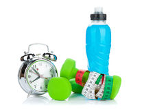 Two green dumbells, tape measure, drink bottle and alarm clock stock photo