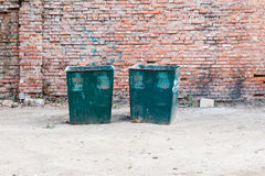 Two green dustbins outside against red brick wall Stock Images