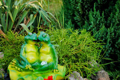 Two green frog figurines sitting in an embrace against a background of green bushes. Two cheerful green frog figurine of plaster sitting in an embrace against Royalty Free Stock Images