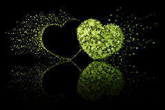 Two green hearts on black background with reflection effect Royalty Free Stock Photography