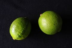 Two green limes against black background royalty free stock photography