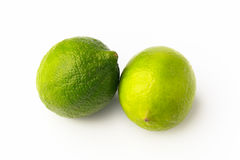 Two green limes. Closeup of two spotted bright green limes Royalty Free Stock Photo