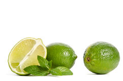 Two green limes and mint with half of juicy lime Royalty Free Stock Photos
