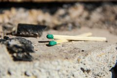 Two green matches on a fireplace or barbecue place. Two isolated matches in focus over each other, forming  an X over a grey backgournd with some ashes and Stock Photography
