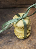 Two green pistachio makarons with green silk ribbon Royalty Free Stock Photography