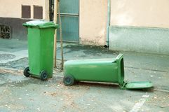 Two green plastic garbage can one is overturned lying on the street. Royalty Free Stock Photography