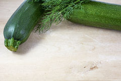 Two green raw zucchinis with fennel on light wooden background Stock Image