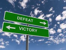 Defeat and victory. Two green sign posts with text 'defeat' in uppercase white letters and an arrow pointing right and 'victory' in white letters with an arrow stock photo