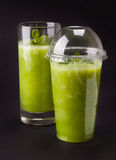 Two green smoothies. Decorated with mint leaves in plastic and glass royalty free stock image