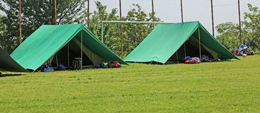 Two green tents mounted in a meadow by the scouts. For their camp stock photo
