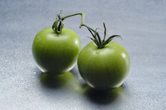 Two green tomatoes. Still life: two green tomatoes on the metal table with drops of water royalty free stock photo