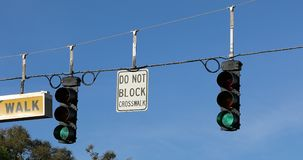 Two Green Traffic Lights Hanging On A Cable. Two Green Traffic Lights And Street Signs Hanging On A Cable Over The Road Against The Blue Sky On International stock video footage