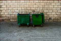 Two Green Trash Dumpsters In Front Of White Brick Wall Front View With Room For Text. Two metal dumpster cans on the side of the s. Quare in ghetto. City green Royalty Free Stock Photography