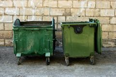 Two Green Trash Dumpsters In Front Of White Brick Wall Front View With Room For Text. Garbage Cans in Front of Warehouse Wall. Two metal dumpster cans on the Stock Images