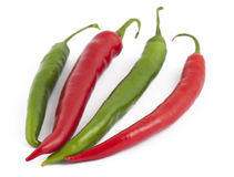 Two green and two red chili peppers on white Stock Photo