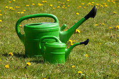 Two green watering can Stock Images