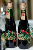 Two green wedding bottles with red wine decorated with flowers, Royalty Free Stock Photos