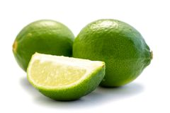 Two green whole limes and lime schnitzels on white background. Green limes lime schnitzels white background fruit fresh food stock image