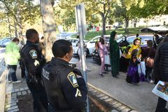Two police officers watch children and adults in Halloween parade stock photos