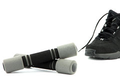 Two grey dumbbells with sneaker on background Stock Images