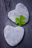 Two  grey heart shaped rocks with leafed clover on a tile Royalty Free Stock Photo