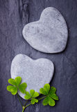 Two grey heart shaped rocks with three lucky clovers on a tile Royalty Free Stock Images
