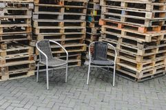 Two wicker chairs placed in front of stacks of pallets stock images