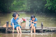 Two gril children sitting and playing water together on wooden b royalty free stock photography