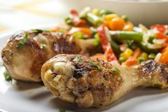 Two grilled chicken drumsticks on palte. Two grilled chicken drumsticks on plate with some fresh vegetables royalty free stock photography