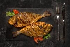 Two grilled dorado fish on dark black granite stone board on black table. Top view stock photo